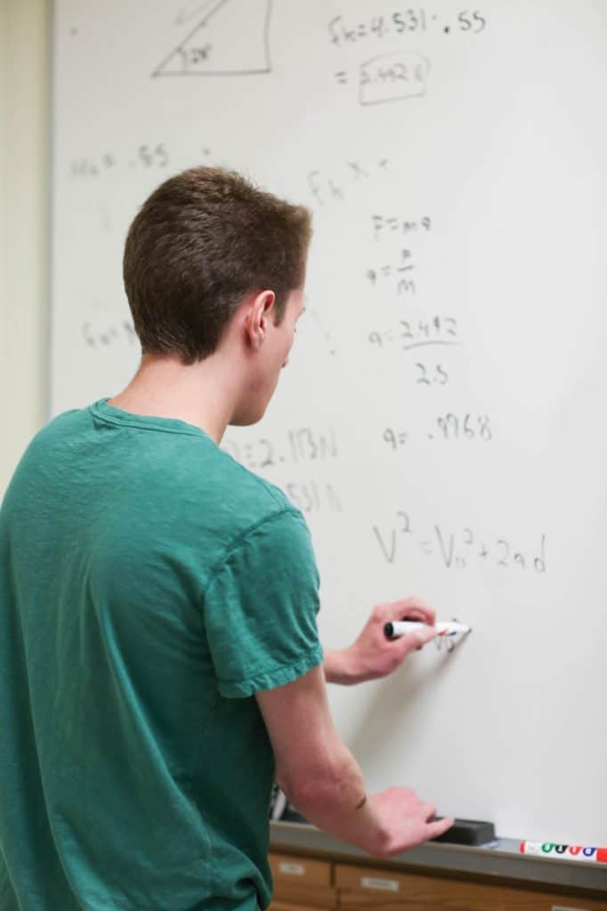 student doing mathmatics on class board