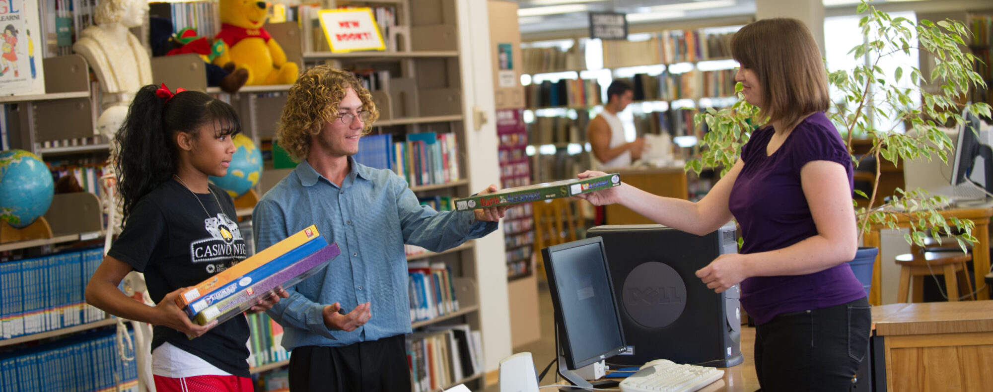 Librarian checking out books for two students