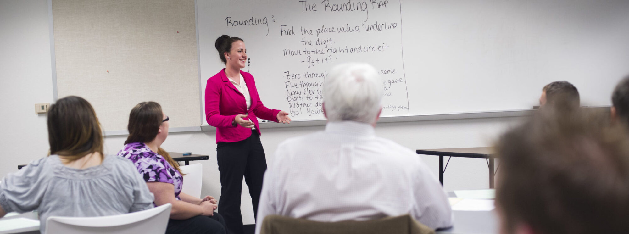 Young woman teaching classroom with the Classroom Rap written on whiteboard in the background.