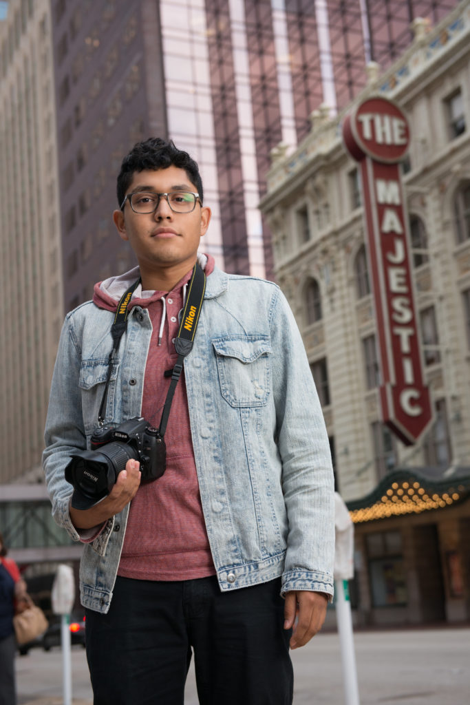 Young man with camera in hand surrounded by tall buildings and a Majestic Theater sign in the background.