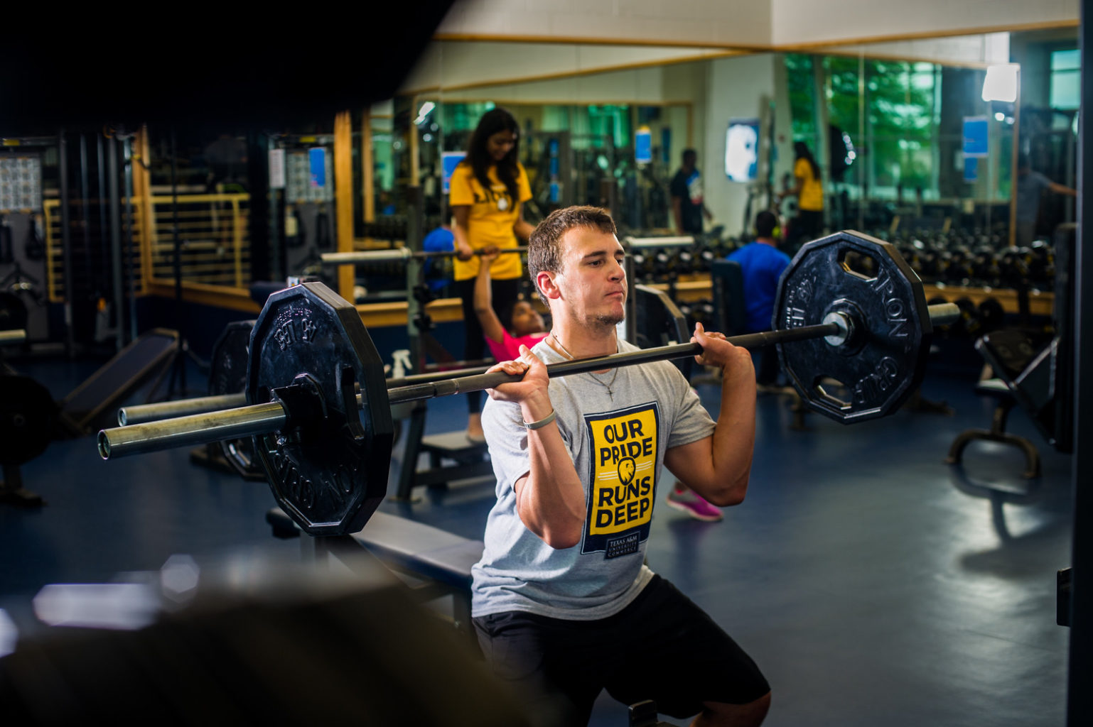 Male student power lifting in rec center