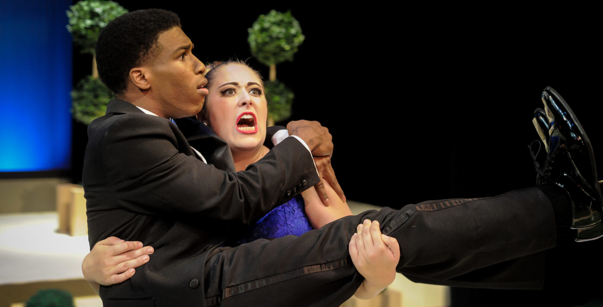 Woman holding a man during a theatrical scene.
