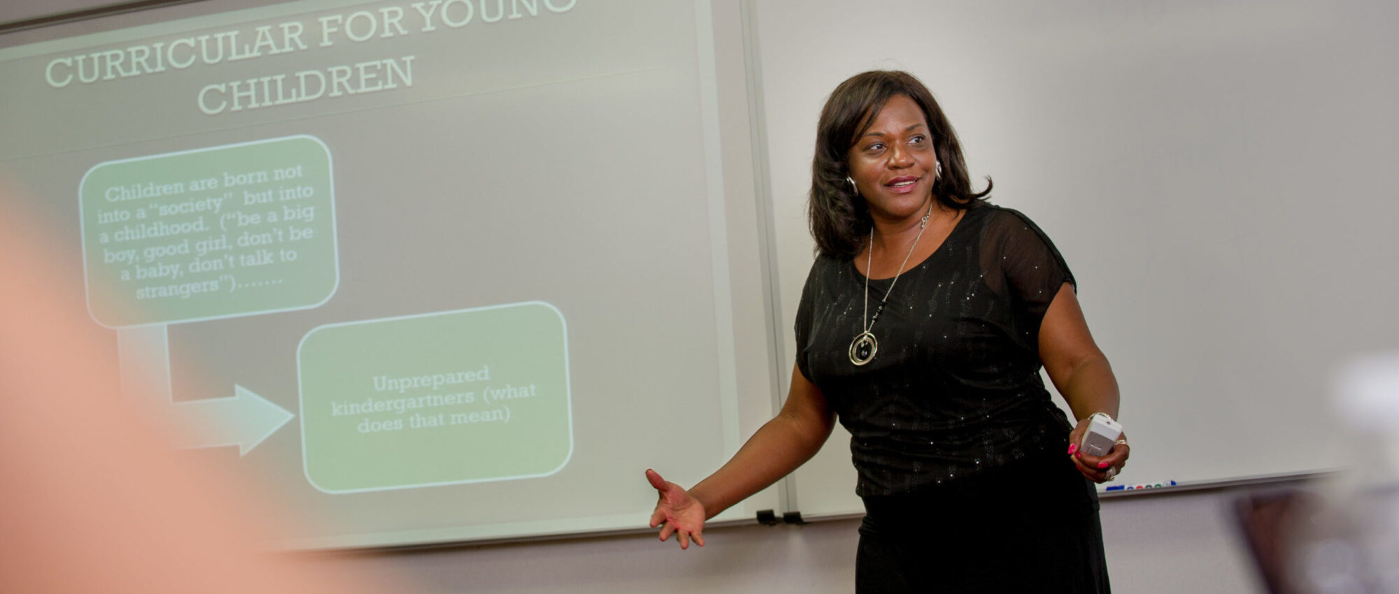 Woman giving presentation to a class.
