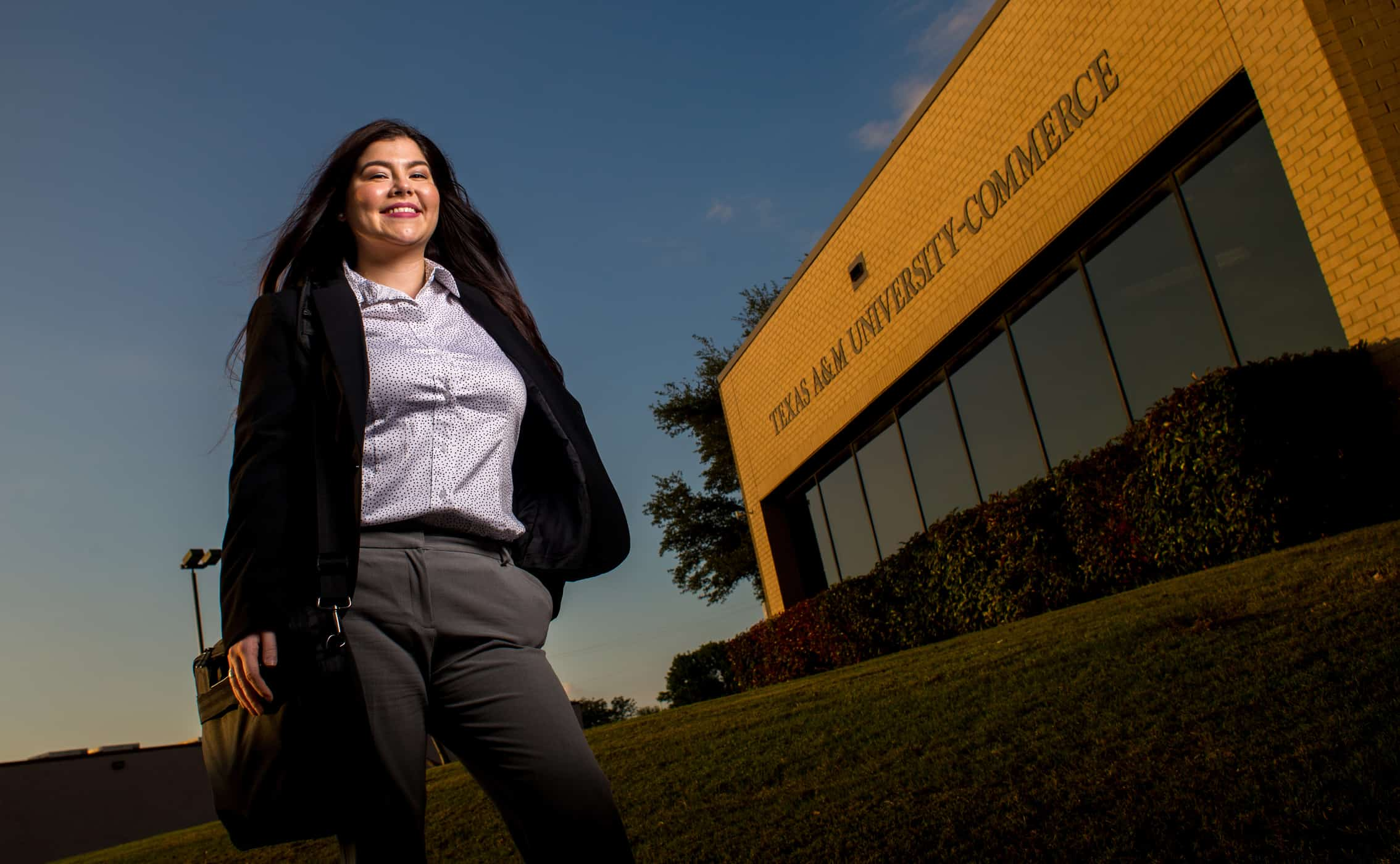 student smiling background 'Texas A & M university-commerce building'