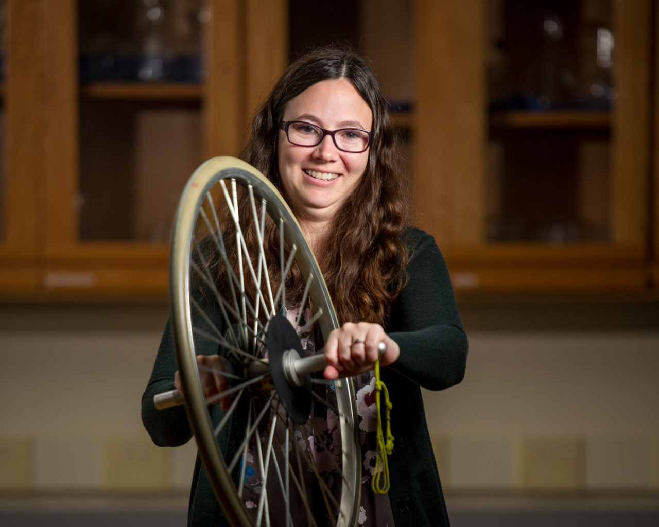 Photo of Robynne Lock holding a bicycle tired used for an experiment.