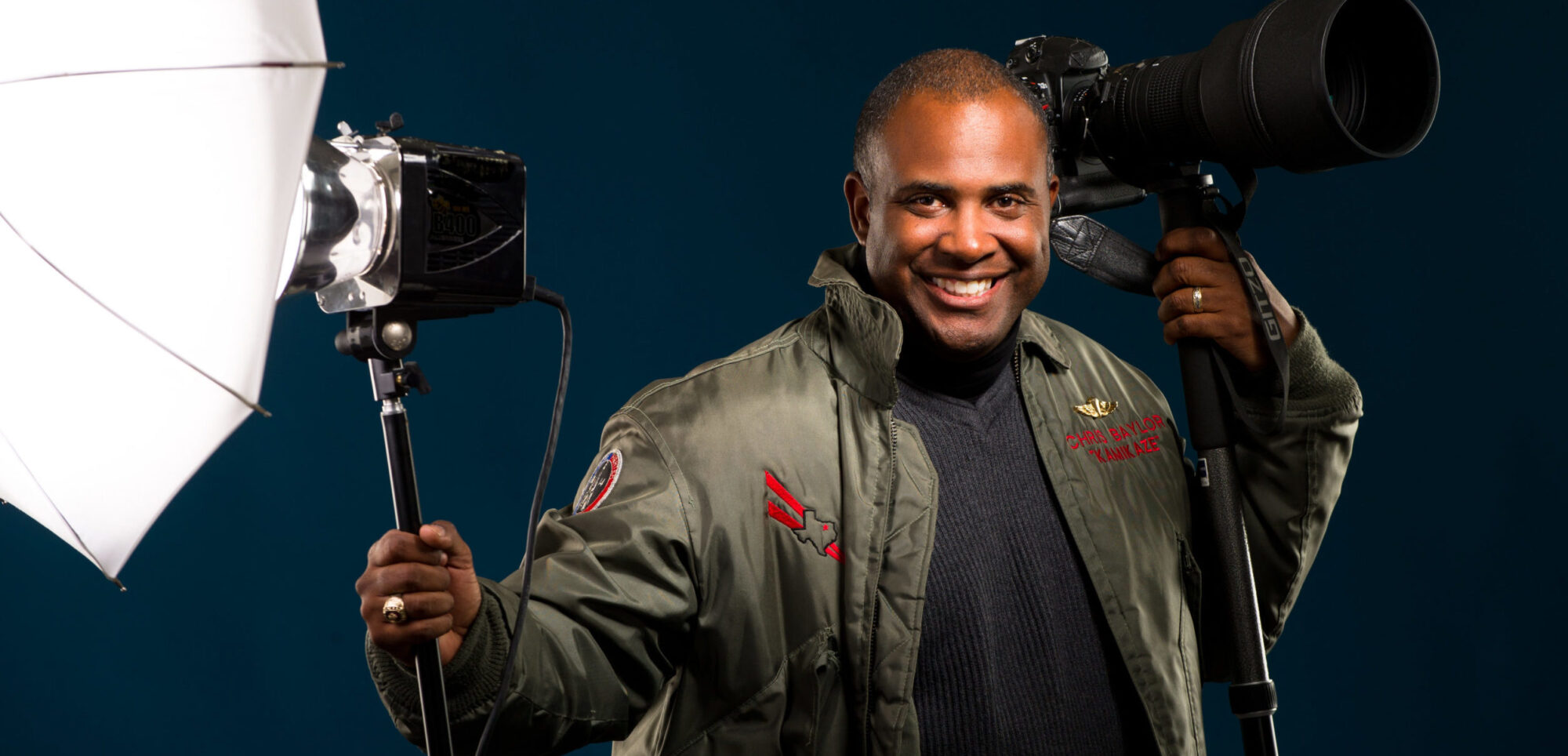 Black male photographer with with camera and strobe in hand.