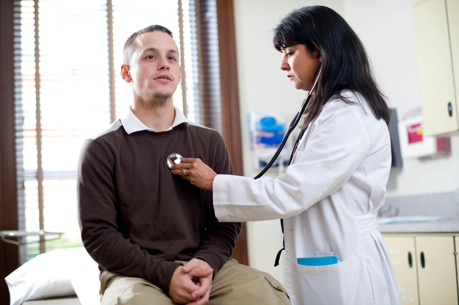 Nurse listening to male patient's heart.