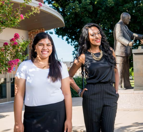 Two students outside background 'Sam Rayburn statue'