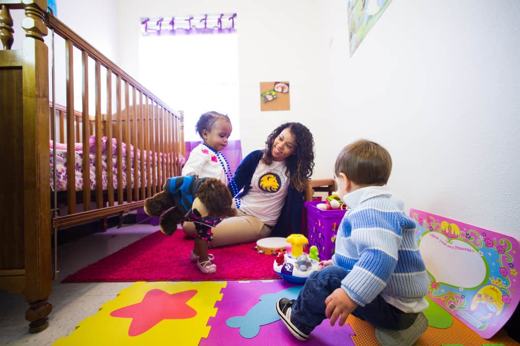 A A&M Commerce student interacting with two kids.