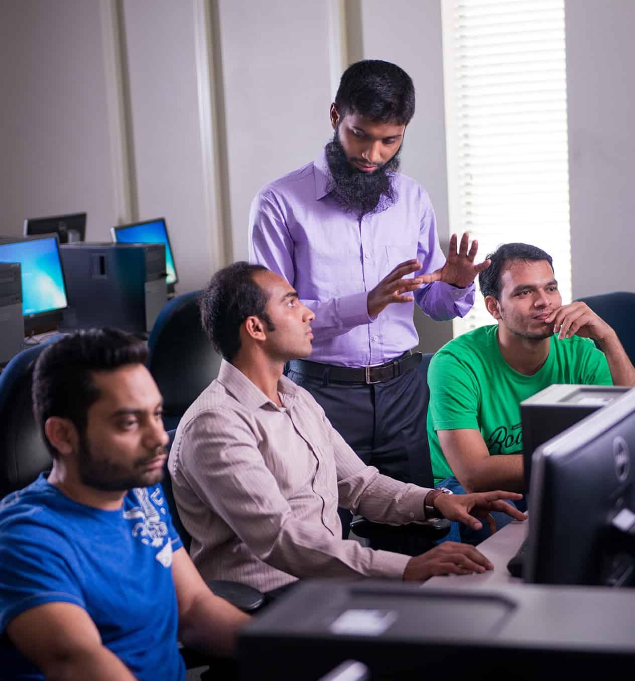 Professor helping three students at computers