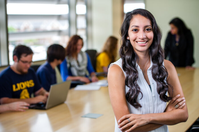 Student smiling posing for photo in front of a desk where other students are sitting down working together.