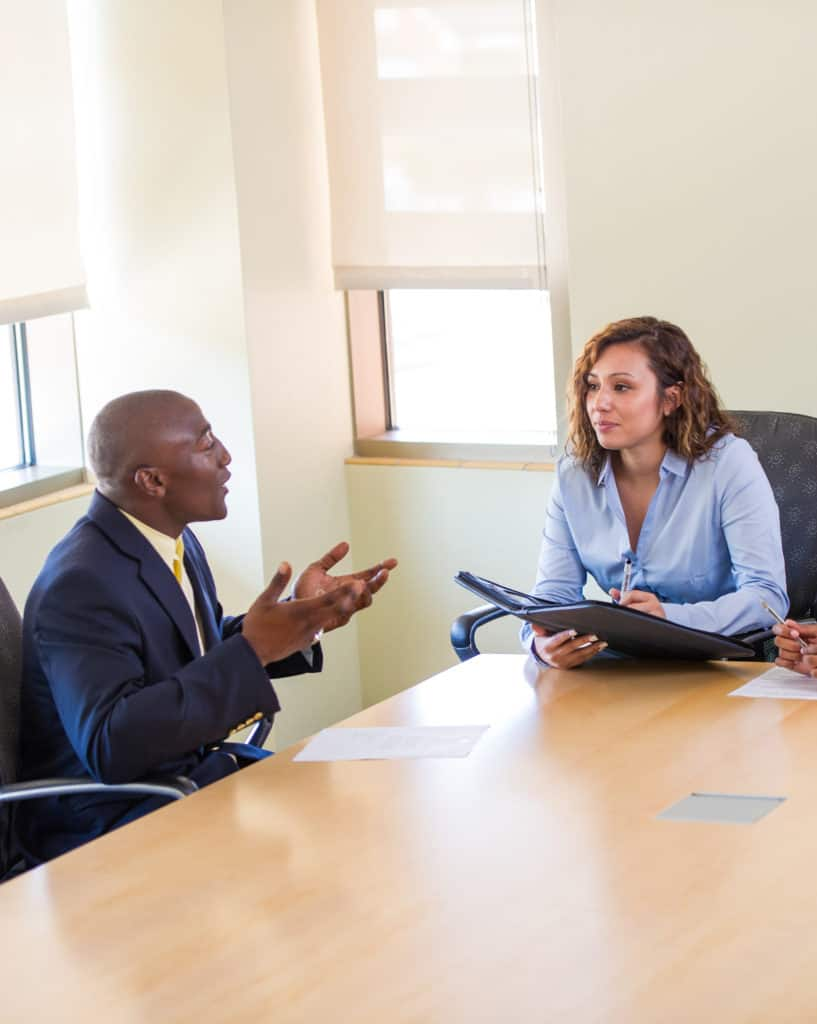 A man and a woman talking to each other sitting down in a conference room.