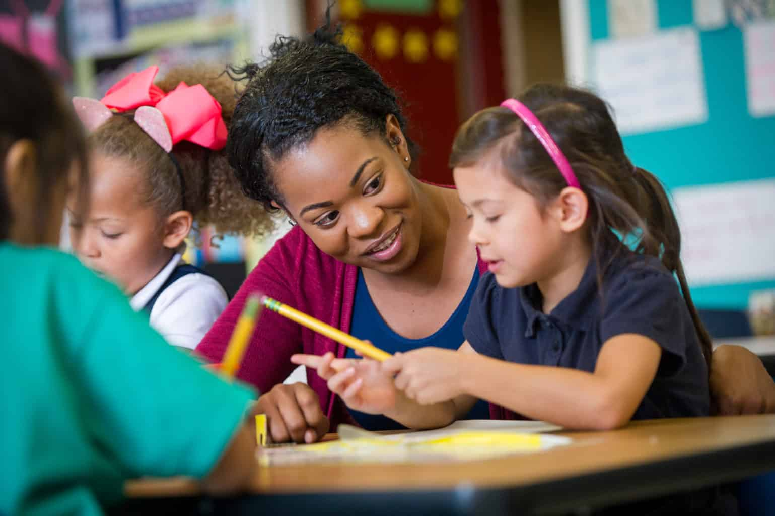 Female teacher with elementary age girl at school desk.