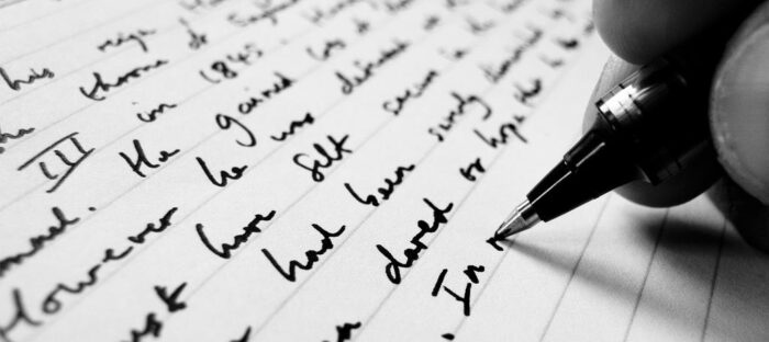 Person writing on a sheet of paper with a pen, zoomed in the fingers holding the pen and the words on the paper.