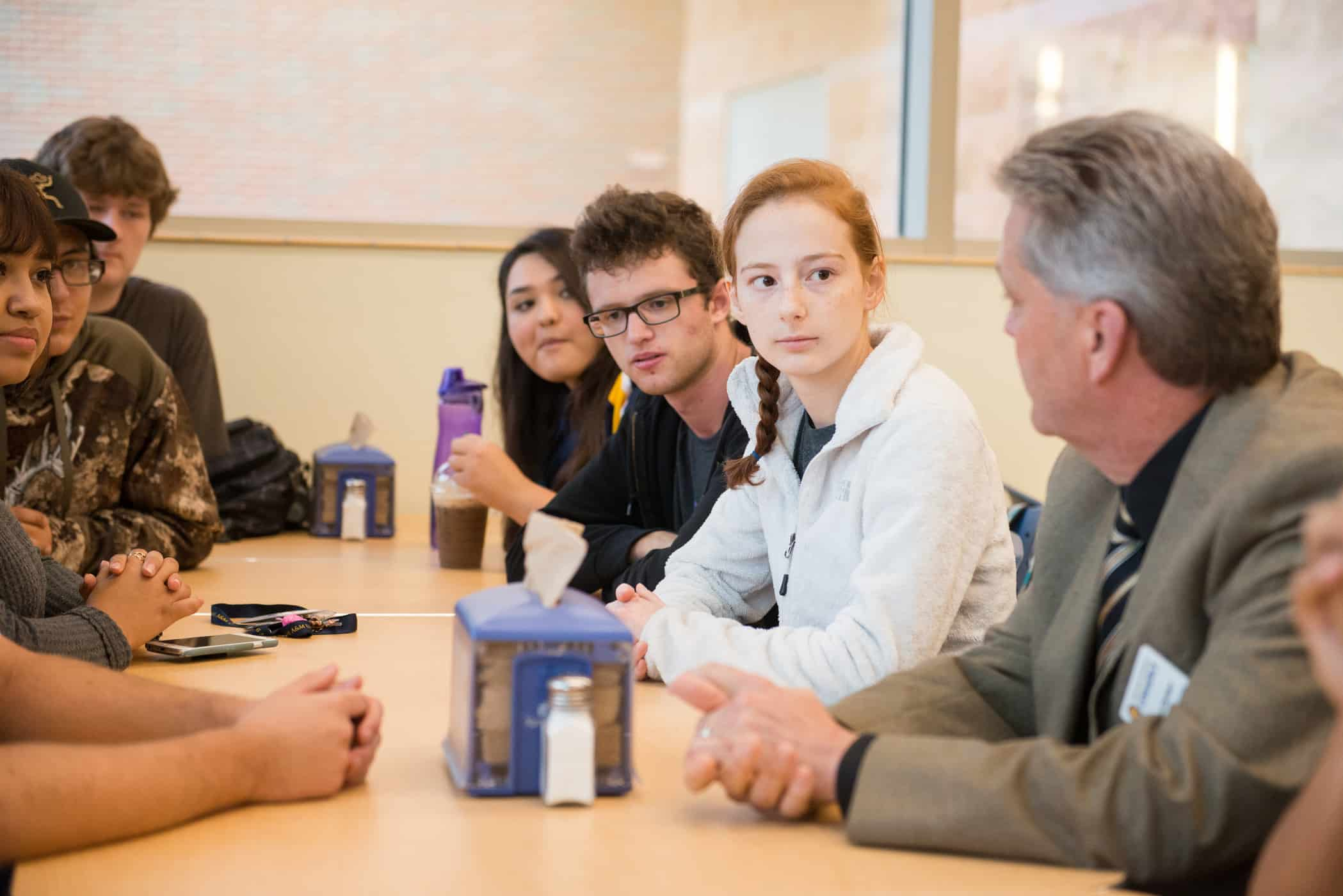 Students sitting with professor at table