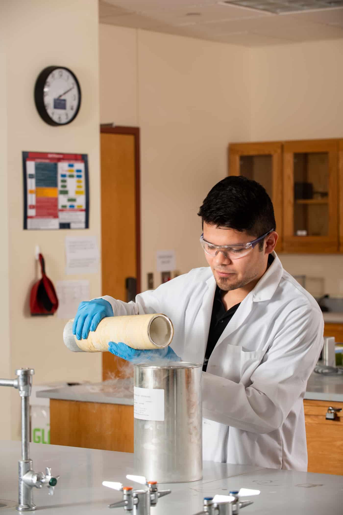 Chemist pouring liquid nitrogen into container