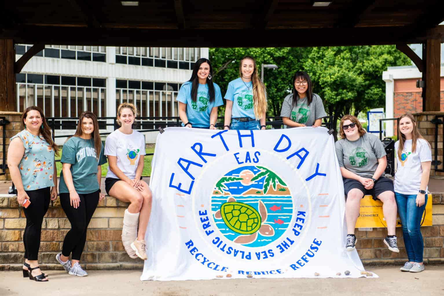 Environmental science students standing with poster