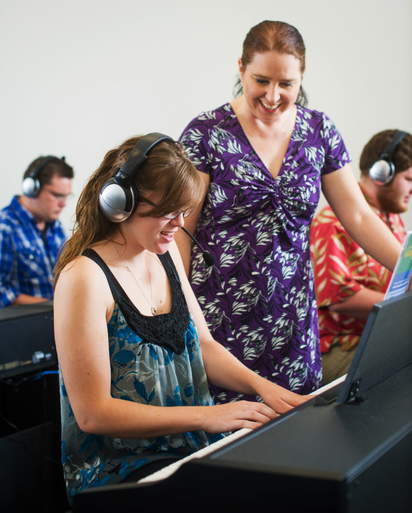 student playing keyboard with instructor observing with smile.