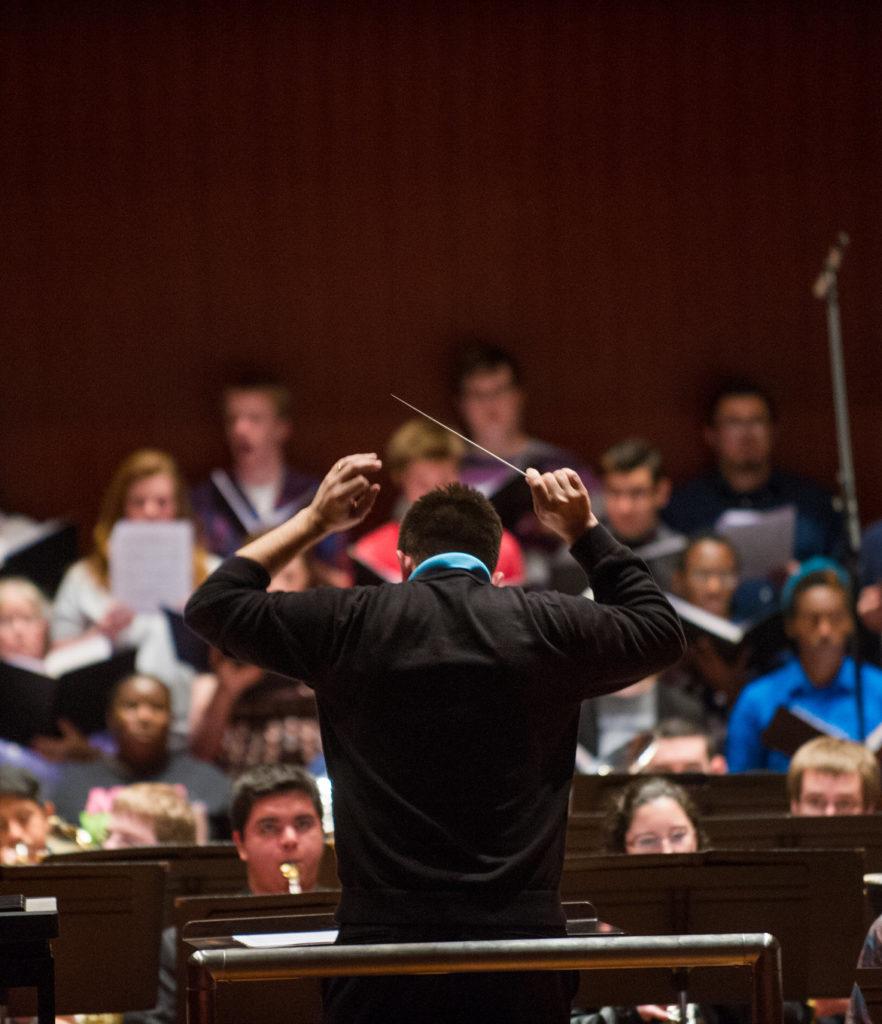 Composer directing a choir.