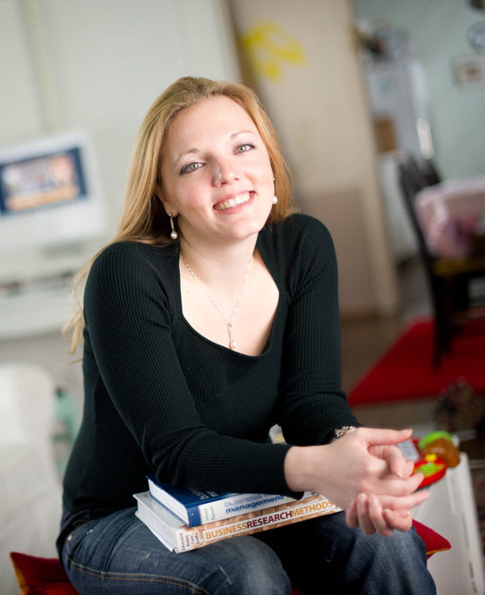 Social worker with books on a couch.