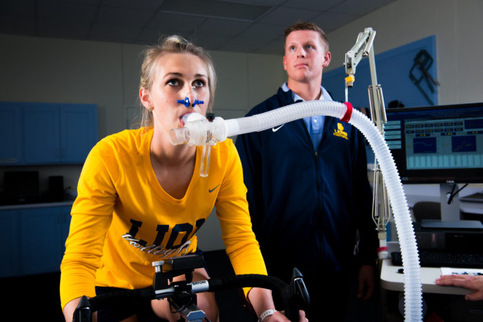 Young lady on exercise bike with ventilator tube measuring oxygen levels.