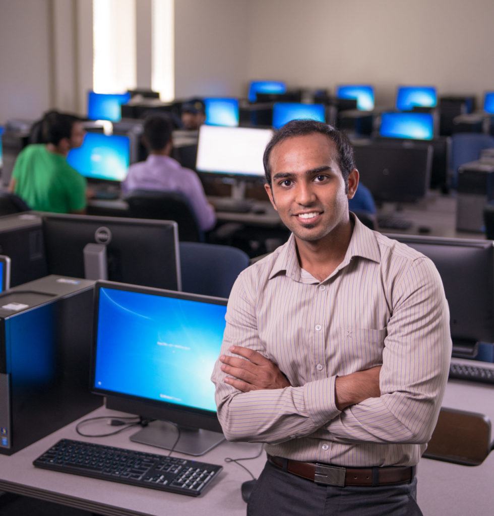 Man standing in front of a computer in a lab.