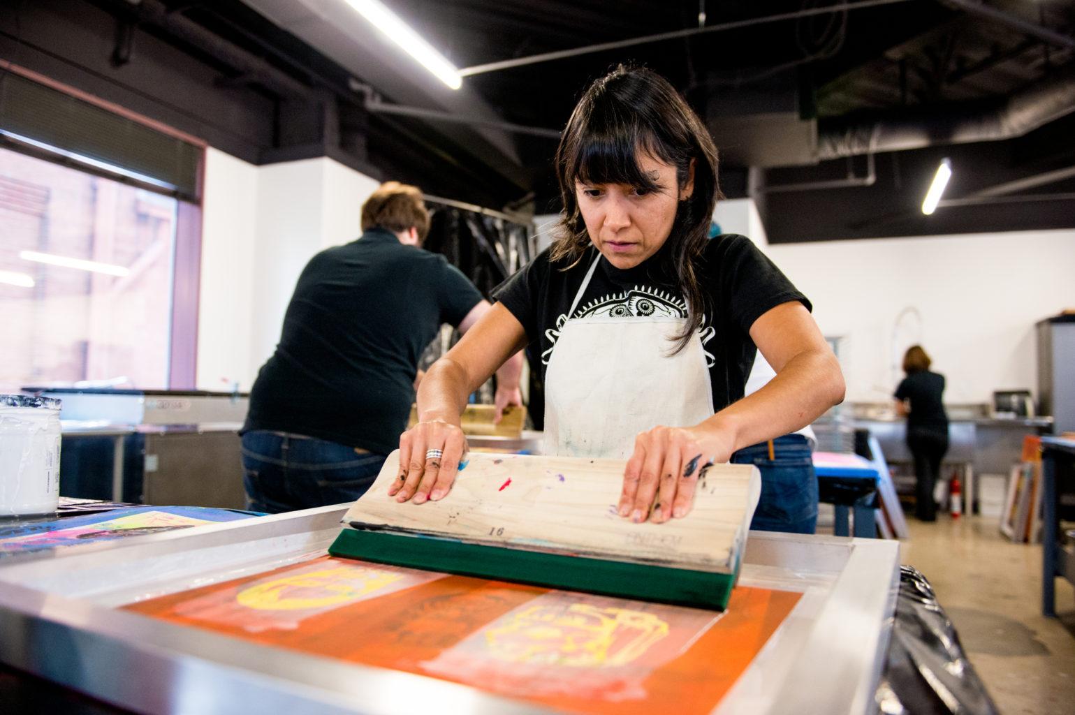 woman screen printing manually