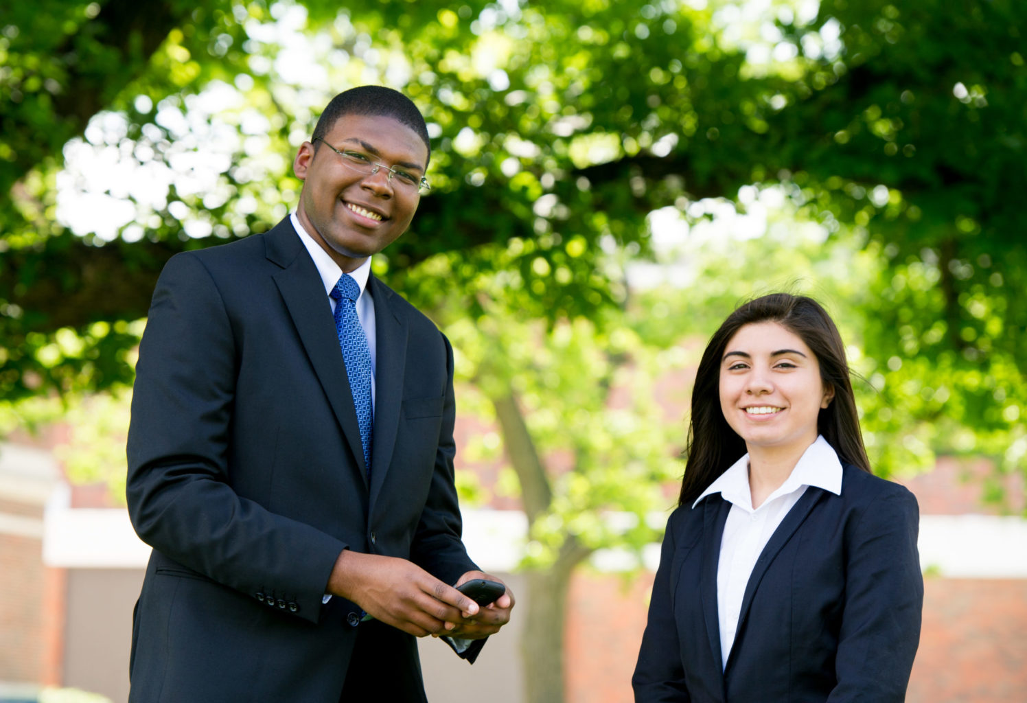 Two students dressed professionally standing outside on campus.