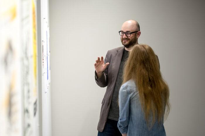 Male instructor explaining art exhibition.