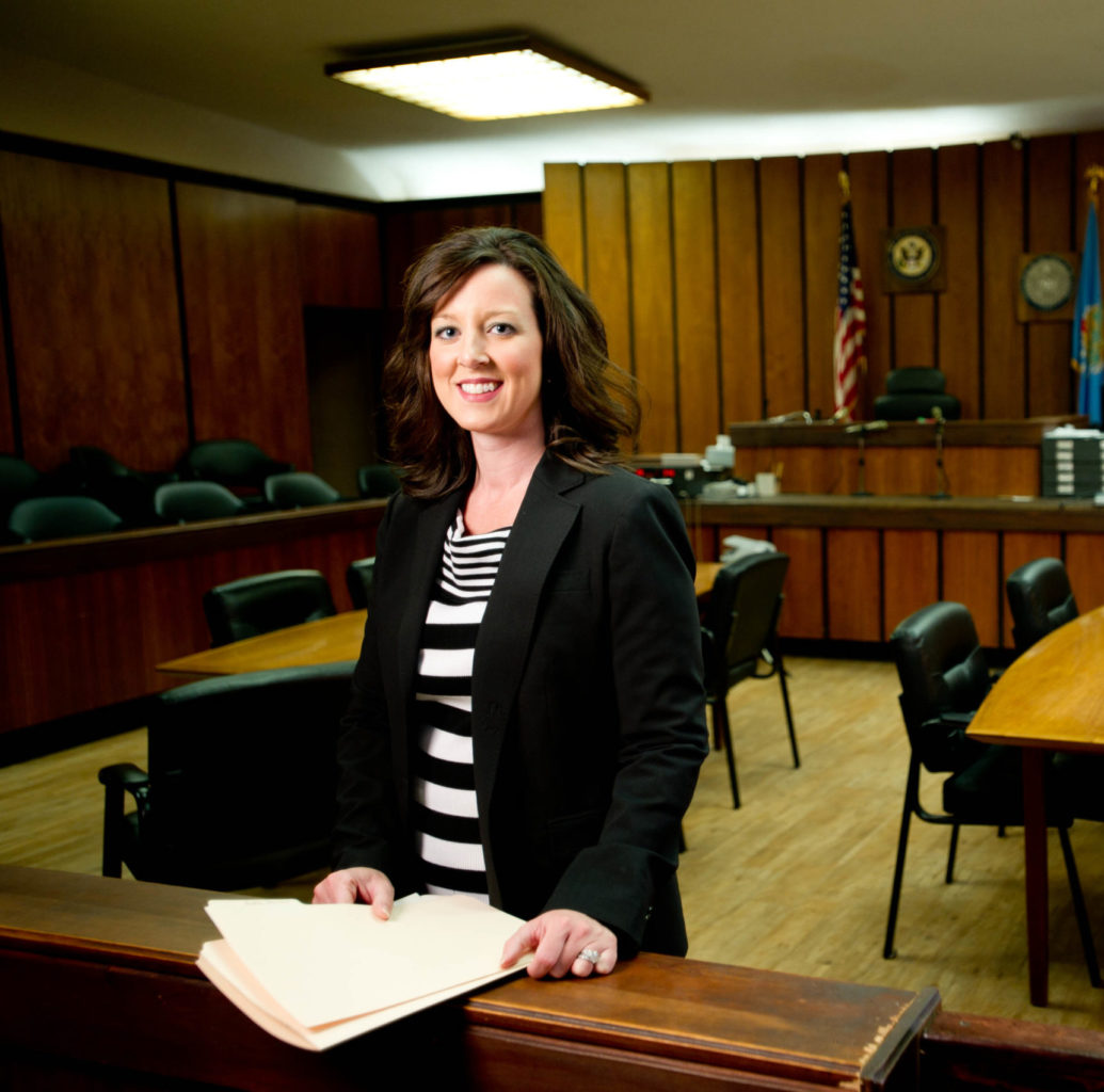 A female dressed professionally standing in a court room smiling at the camera.