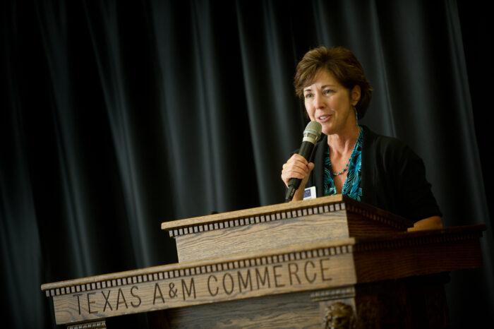 Woman teaching at a social work gala.