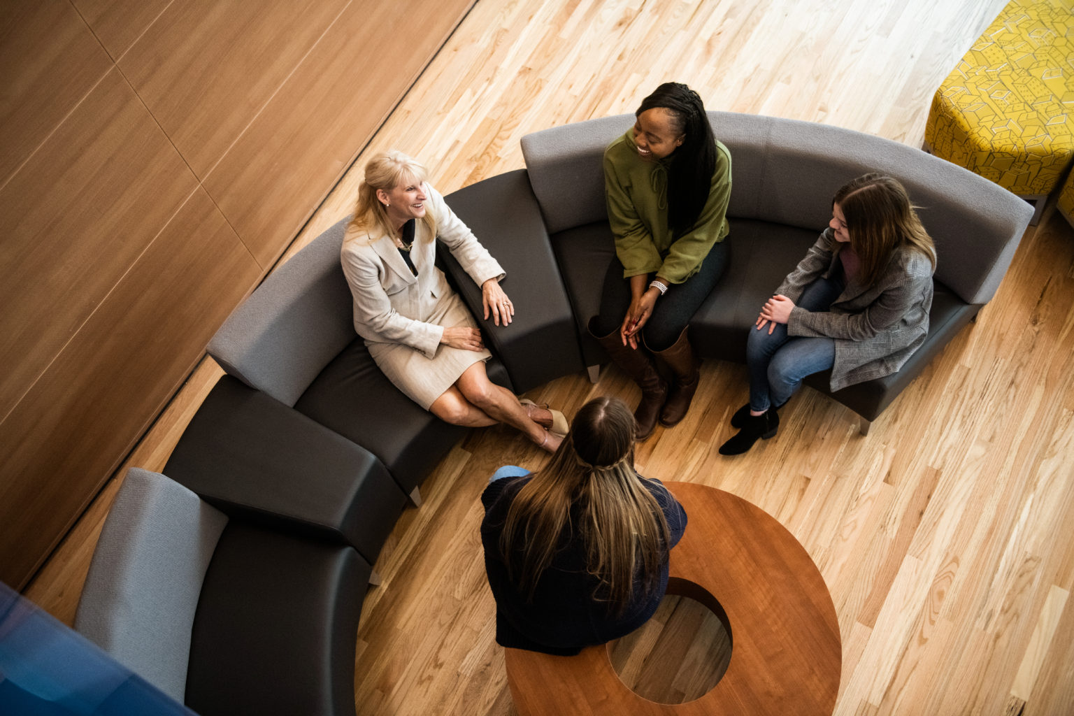 A teacher talking to a small group of student in the common area in the new health sciences building.