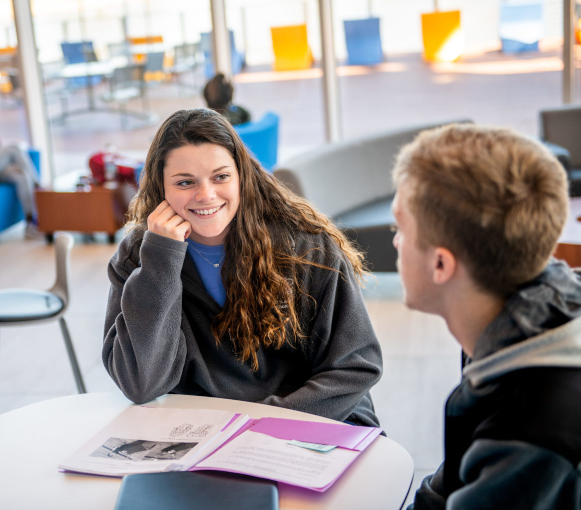 Young woman speaking with man in classroom environment