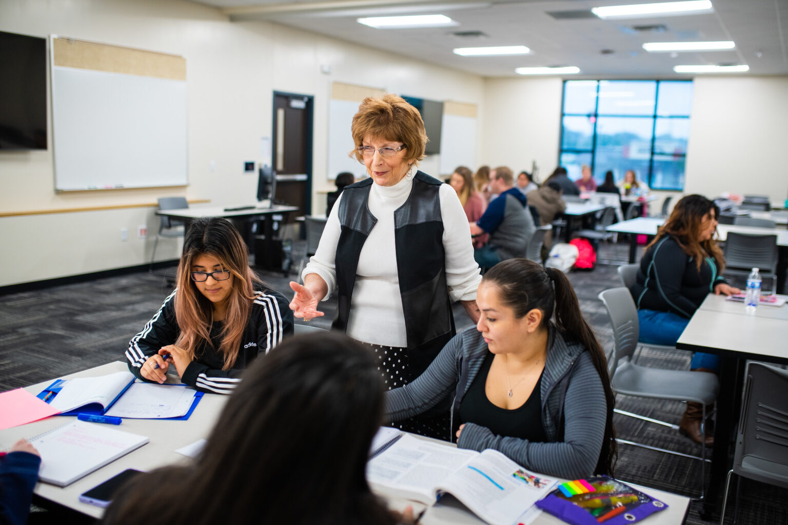 Faculty member working with college students in a large classroom