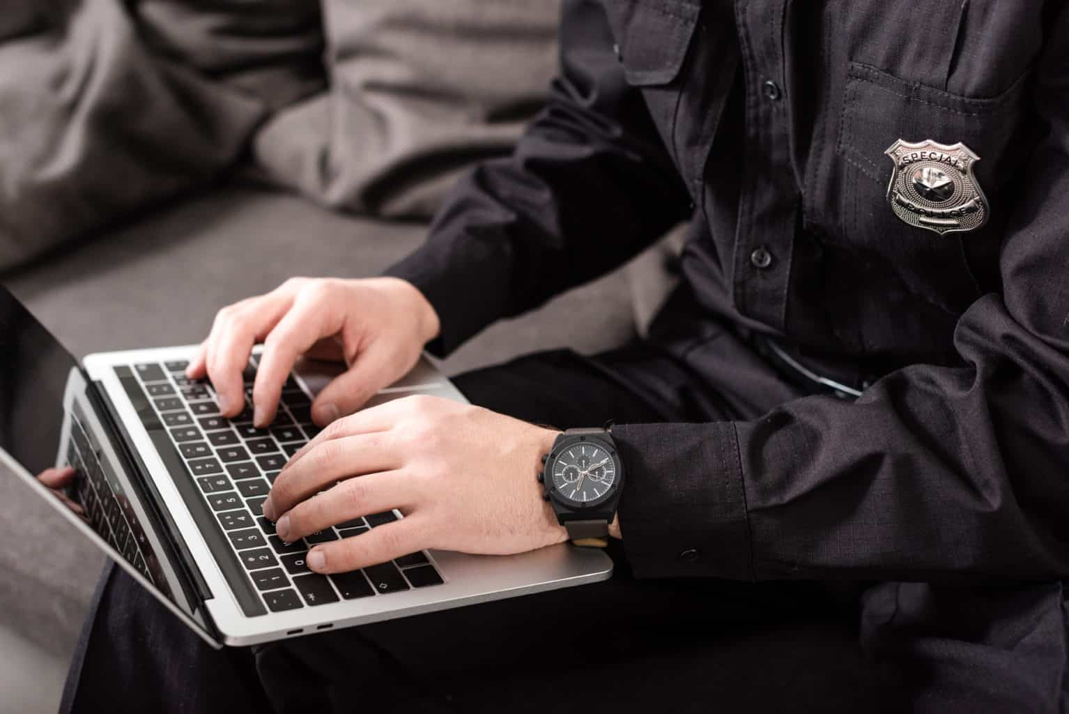 cropped view of policeman typing on laptop keyboard