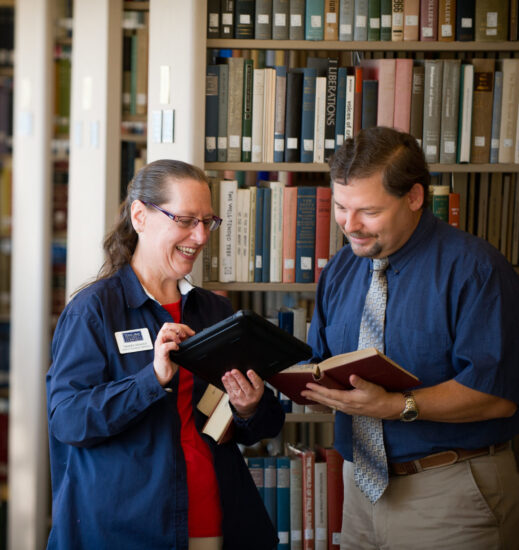 Two librarians standing in a library.