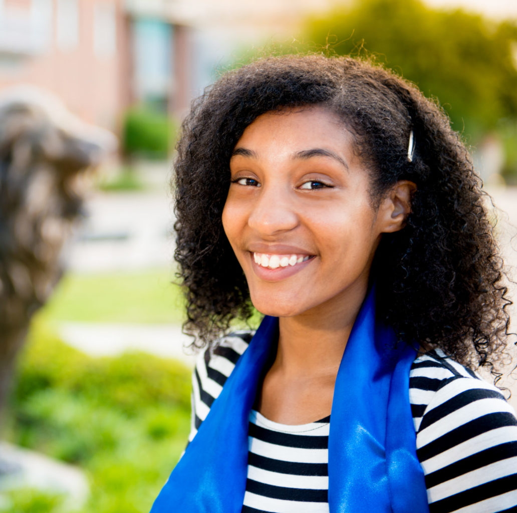 Young woman smiling while standing in front of university lion statue.