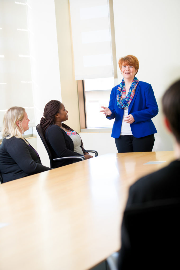Business dressed woman speaking to group around a large table.
