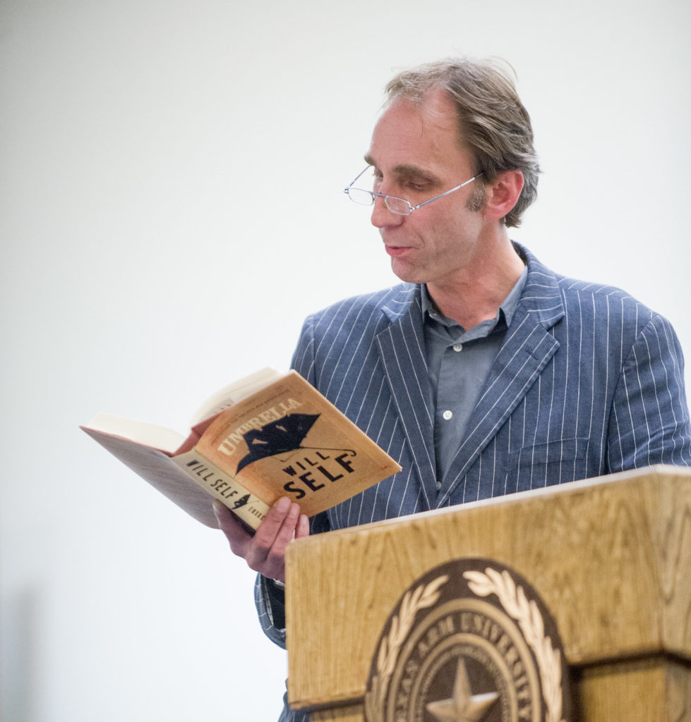 Man reading book from podium.