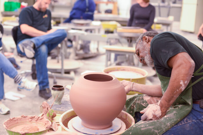 the professor creates a ceramic vase in front of the students.