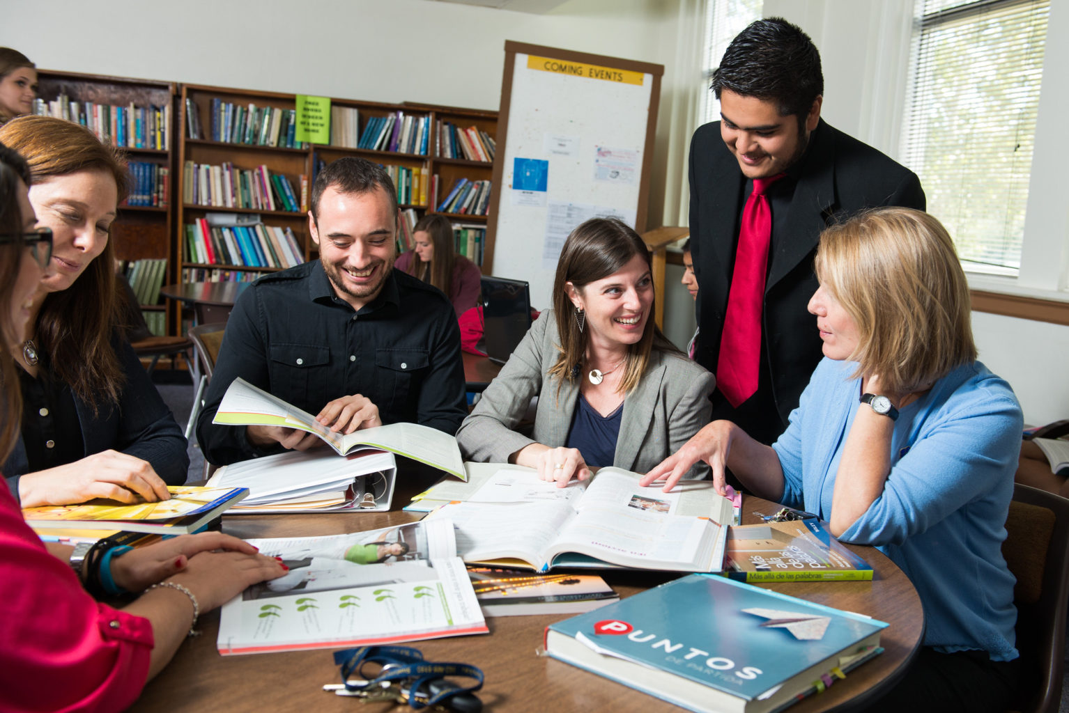 group of graduate students gathered around a table with spanish book labeled Puntos.