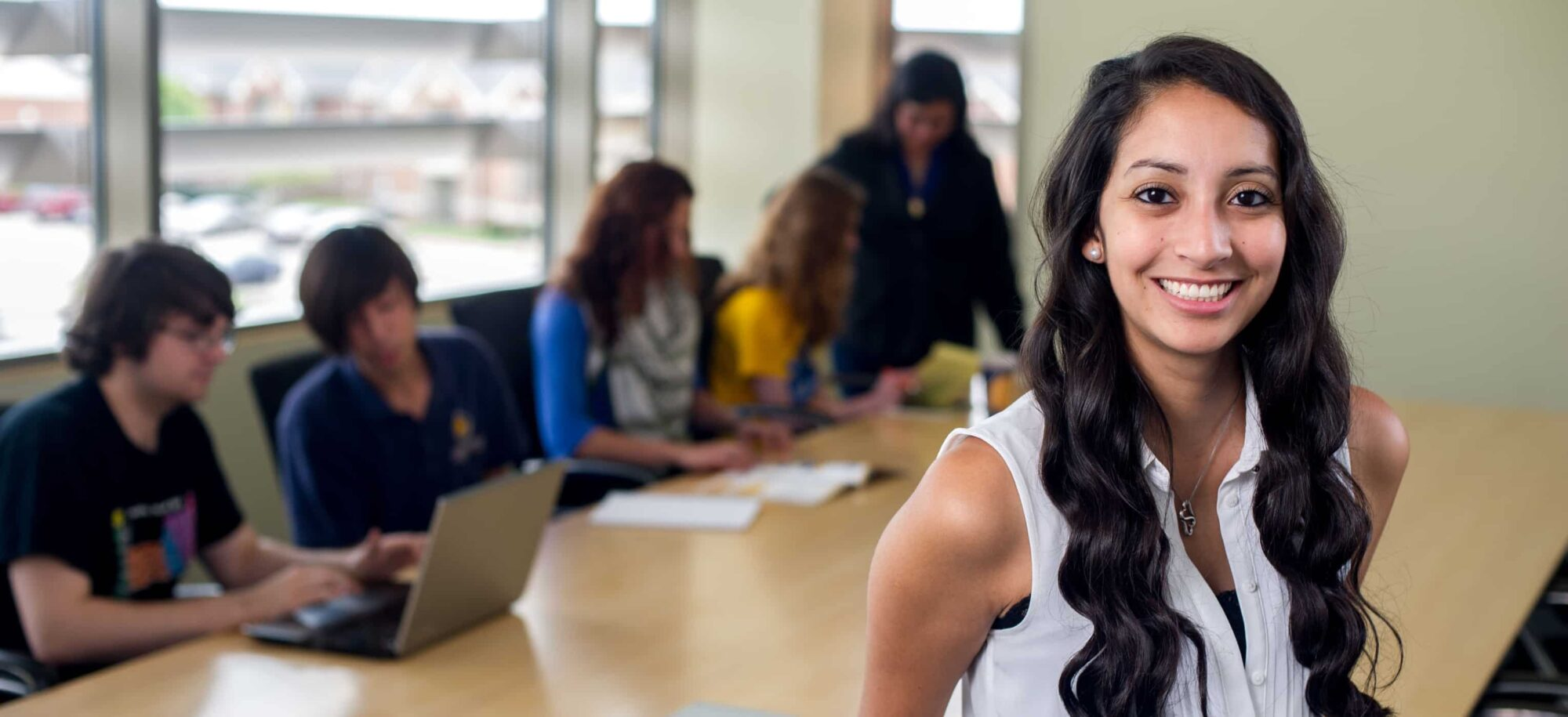 Business student smiling in front of classmates