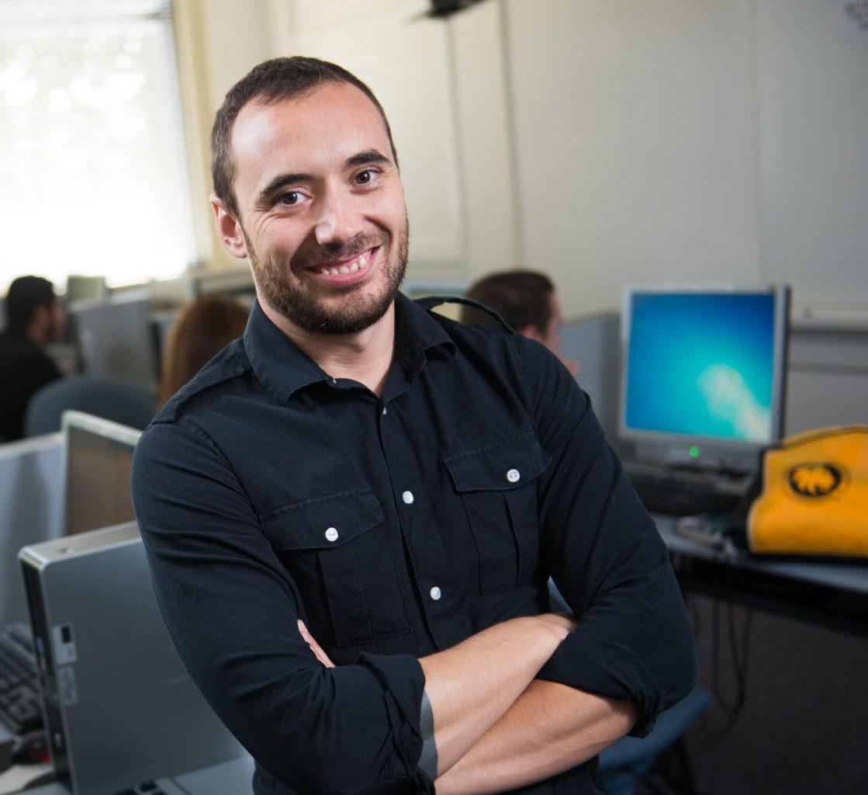 Hispanic man standing in computer lab.