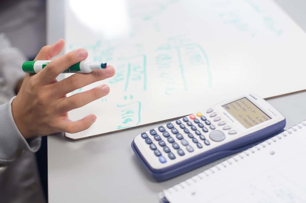 Image of calculator and someone holding a marker.