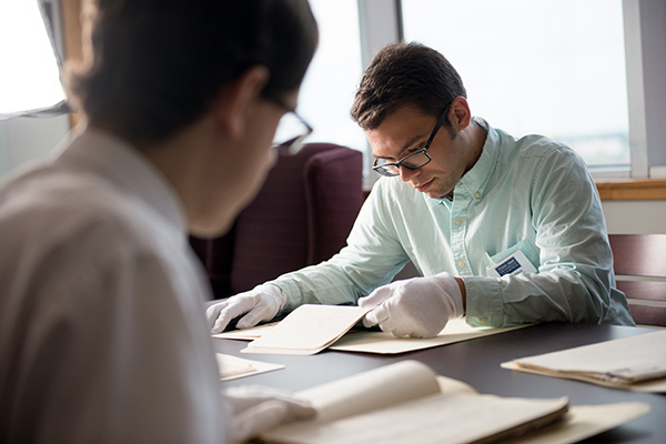 Two students looking over historical documents using gloves.