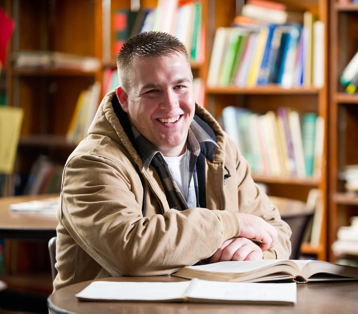 Man sitting at desk in library.