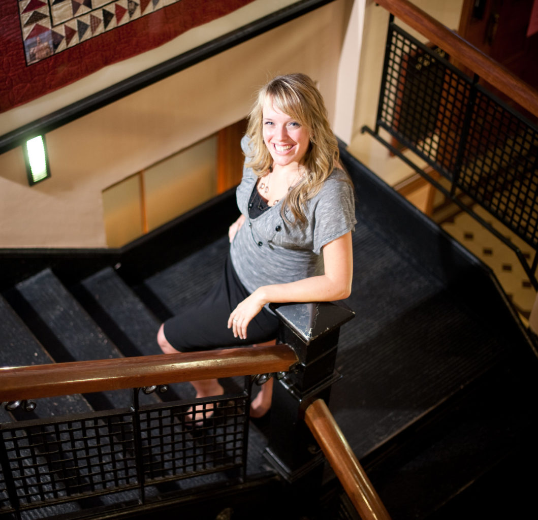 Woman standing on interior stairs of courthouse.
