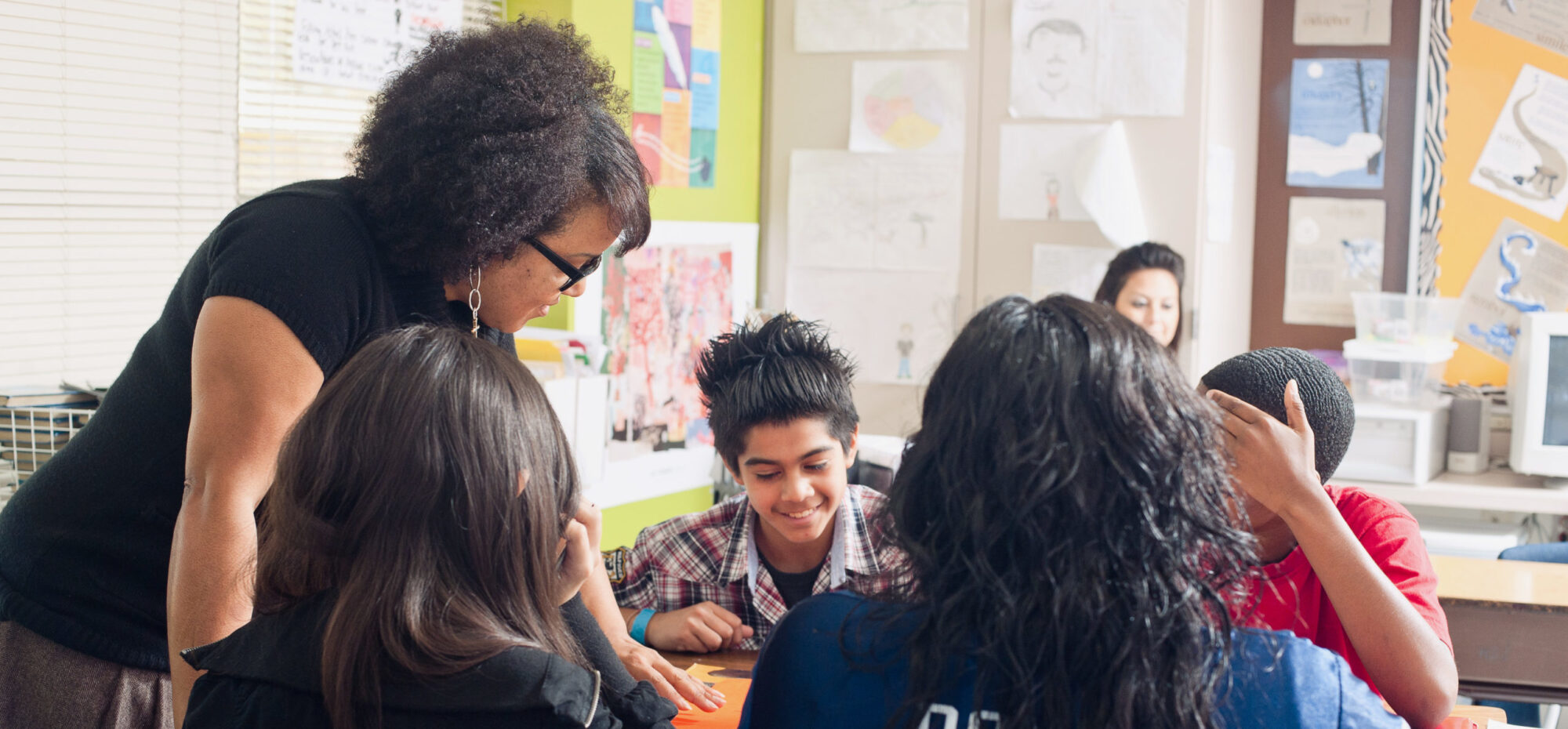 Female teacher working with high school students sitting in desk facing one another.