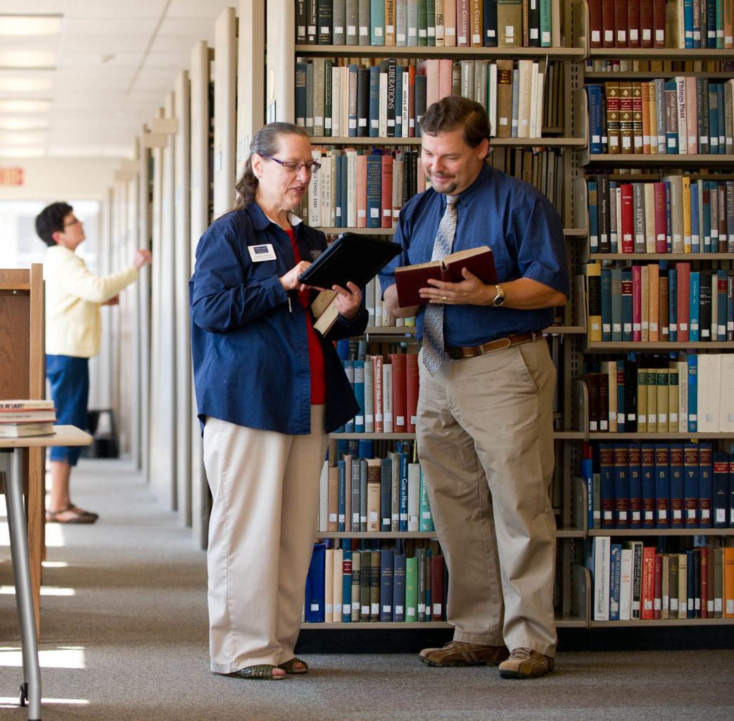 Two people examining books in a library.