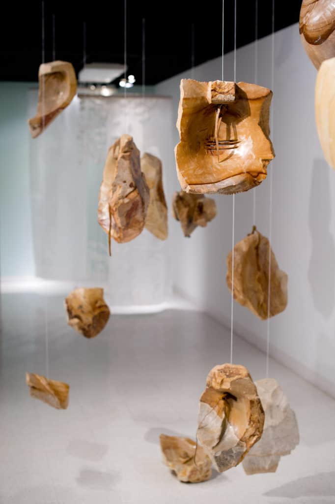 Broken pieces of pottery suspended from clear line.